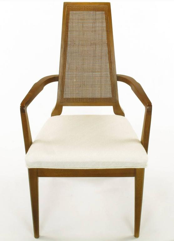 1950s Modern set of six Danish weave cane back dining chairs. Finely carved walnut frames with uncommon details such as the curved narrow backs and sculptural legs. Upholstered in a woven Haitian cotton with relief detailing.