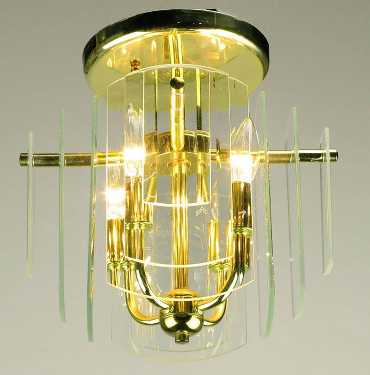 A pair of brass four-arm ceiling lights with four sides of graduated and beveled glass. Each side features three layers of glass plates that step down in size from the center. One of three pairs available.