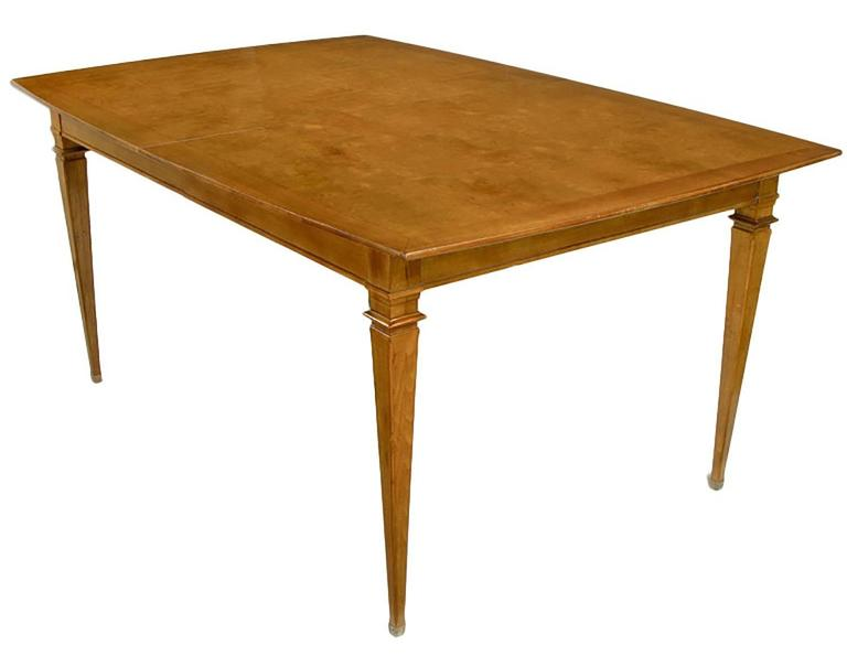 Elegant burled walnut and copper accented dining table. Slight boat style bow to the walnut bordered patchwork burled parquetry top. Walnut extreme tapered legs with patinated copper sabots and capitals. Possibly early Mastercraft or Landstrom