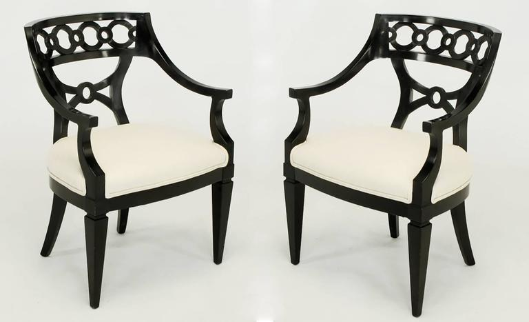 Beautifully carved armchairs in the manner of Baker or Kindle with Curule lower back panel beneath a top of curving carved wood rings. Tapered front legs with saber back legs. Overall very good condition with new white wool upholstery.