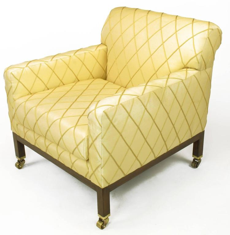 Edward Wormley for Dunbar club chair with rolled back, ash wood Parsons style legs with solid brass sabots and castors. Older saffron silk upholstery with embroidered harlequin pattern in very good condition. Second matching chair in need of