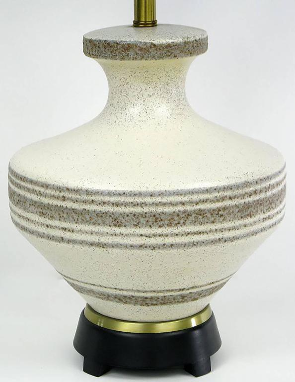Hand thrown pottery table lamp attributed to Lightolier, with oriental urn shaped ceramic body glazed in speckled cream with taupe banding stripes. Three socket cluster which was a configuration most notably used by Lightolier. Black lacquered wood