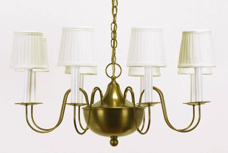 Very well designed and finely constructed spun brass bowl eight-arm chandelier. Nods to French Regency styling with the slender brass S shaped arms with petite disc bobeches, spun brass bowl with flanged cap and large closed ringed finial.