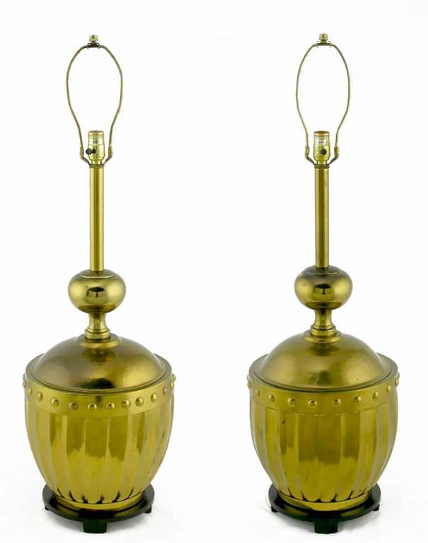 Large studded and fluted brass table lamps from the best years of Stiffel, the fine lamp maker. Black lacquered bases feature subtle chamfered feet. Surmounting the brass urns are brass post and ball columns. Sold sans shades.