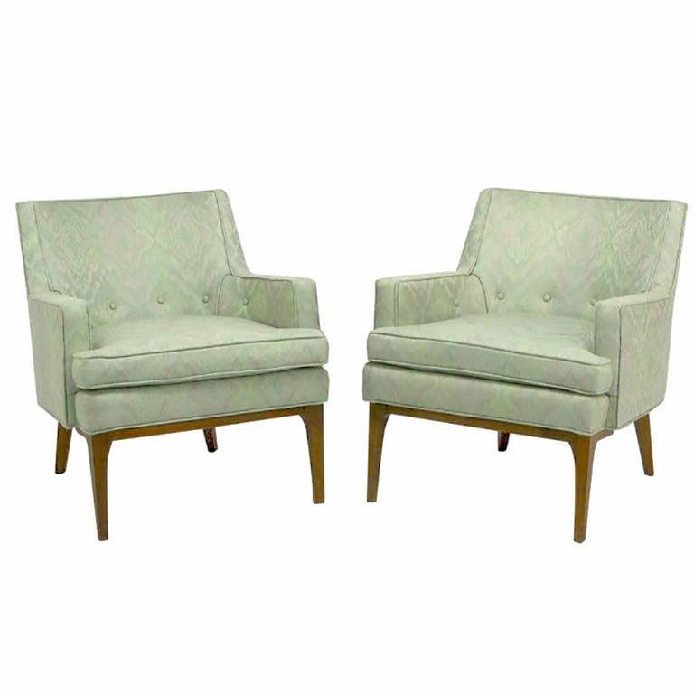 Clean lined pair of Classic club chairs in the manner of Jens Risom. Aquamarine and lavender Ikat patterned silk blend upholstery. Walnut wood legs with sculptural front apron and radiused corner legs. Loose seat cushion, and button accented back