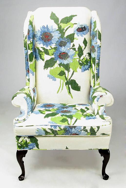 Elegantly modern pair of wingback club chairs from Hickory Chair Company. The oversized floral print linen is comprised of green, blue red and black flowers on a white ground. The front legs are cabriole carved mahogany and the mahogany back legs