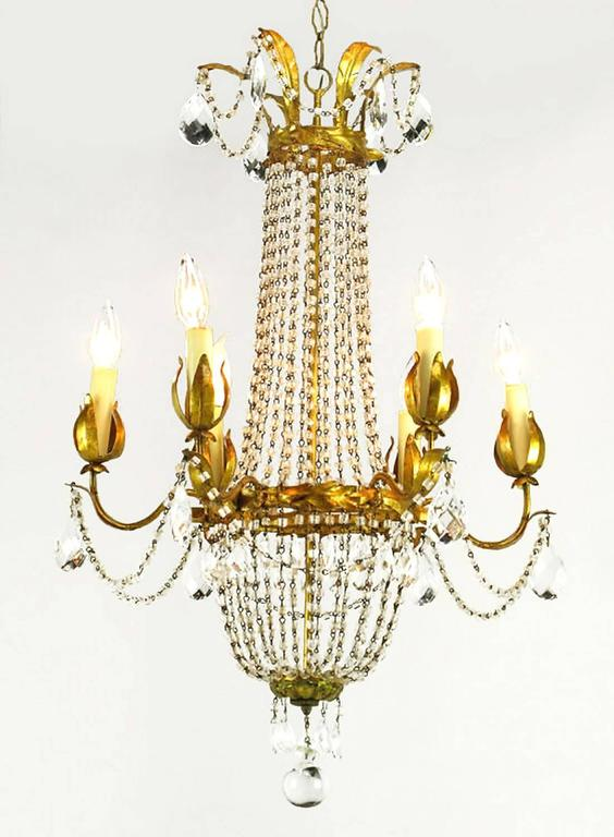 Elegant gilt Italian tole metal and iron crystal basket form chandelier with six arms. Adorned with real wax and pressed paper tube candles, draped with cut pear-shaped crystals and crystal strands. It is finished with a large crystal sphere
