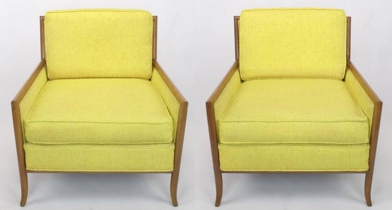 Pair of bleached walnut and cane sided club chairs covered in canary yellow Haitian cotton. Often attributed to T.H. Robsjohn-Gibbings with several design points common to his work with Widdicomb. Saber front legs, radiused walnut frames and raked