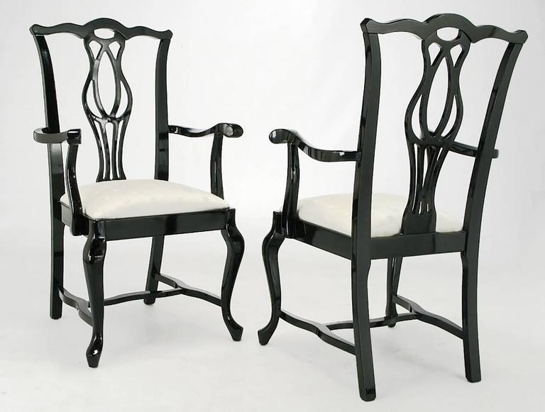 Set of six Chinese Chippendale style black lacquer over hard wood dining chairs with off white silk blend upholstered seats. Set includes two armchairs and four side chairs. Excellent carving from the sinuous stretchers to the cabriole front legs to