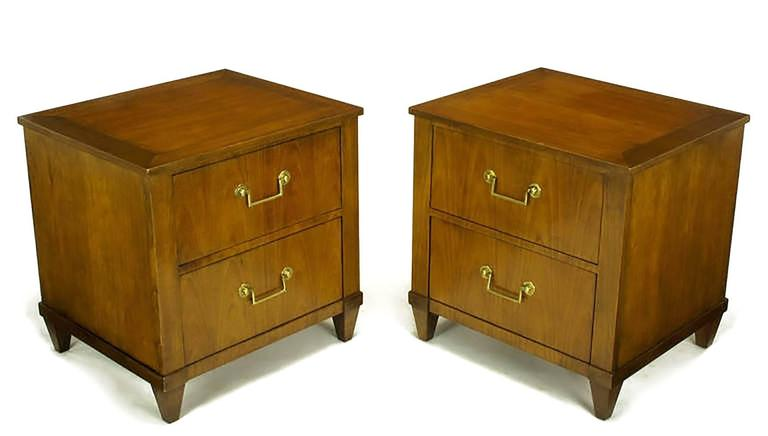 Unusual pair of Baker nightstands in figured French cherry, with brass bail drop pulls and round escutcheons. Transitional style with a single drawer and a fall front storage space above. Could also be used as end tables as they are finished on all
