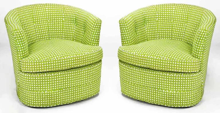 A striking pair of barrel back chairs in the original button tufted, wool needlepoint fabric. Strikingly upholstered in vivid geometric chartreuse, green, gold and white. Low swivel mechanism is nearly fully concealed, making the chairs appear as if