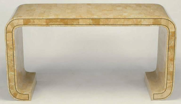 Tessellated coral stone over wood console table with brass inlay by Maitland Smith. Water fall design with turned legs, and finished on both sides. Made in the Philippines, where Karl Springer's similar designs were manufactured.