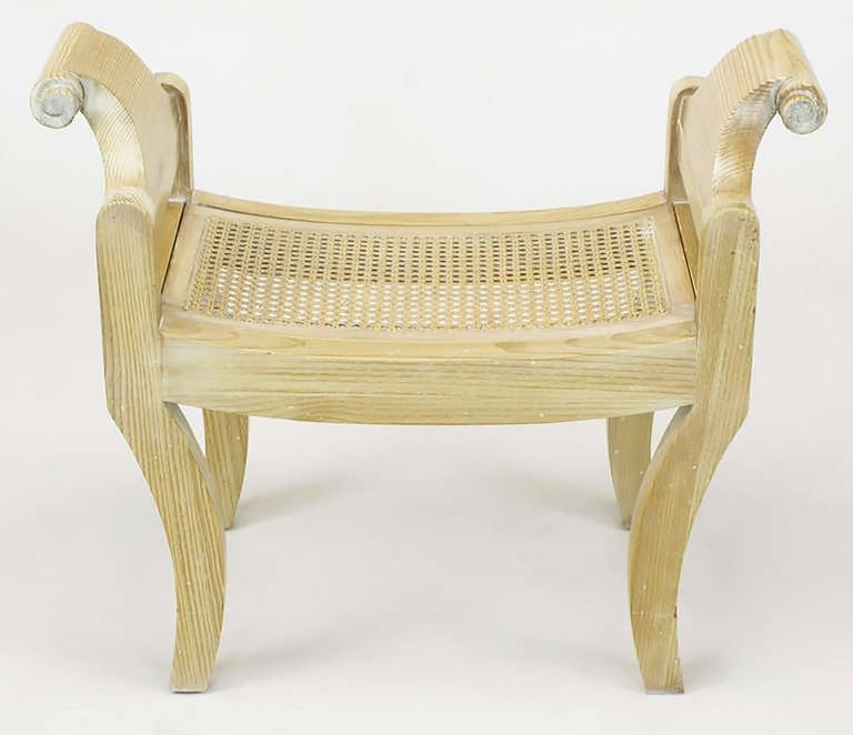 Pair of Swedish Rococo style pine benches with klismos form legs, scrolled arm handles and curved cane seats. Constructed from white pine, glazed in white and restored with patina left intact.