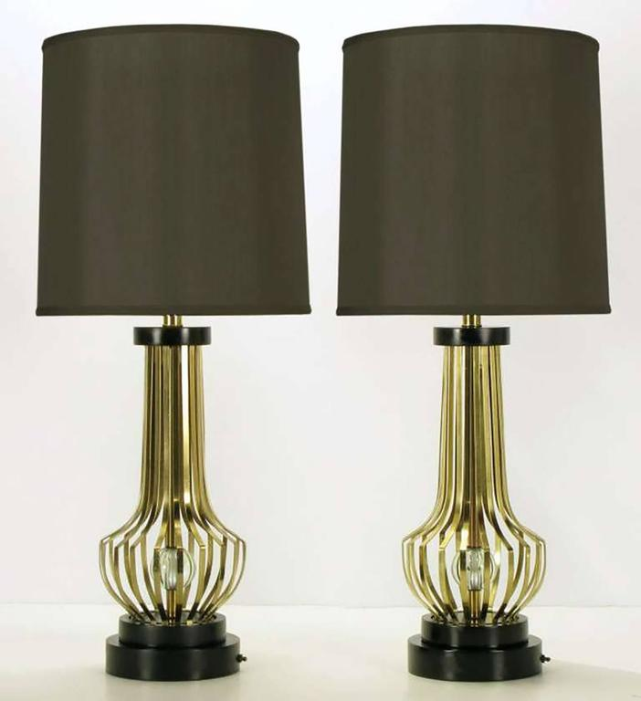 Pair of vase form open rib table lamps with internal crystal spheres. Black lacquered and stepped round disc bases with switch and black lacquered disc cap. Original milk glass diffusers on large brass cups. Unmarked, but milk glass diffuser and