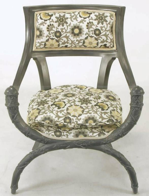 Pair of uncommon Curule front arm chairs in updated slate gray lacquer over wood. Seats and backs are upholstered in a modern gray and saffron print on white cotton. Deep sloped arms and rear saber legs complement the rounded seat and carved vine