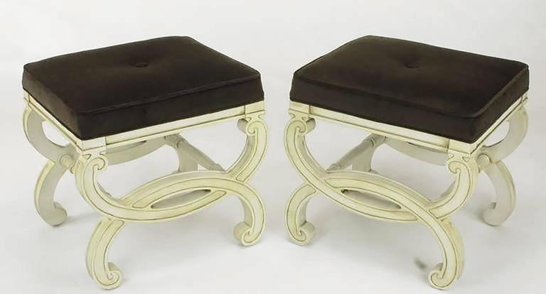 Restored pair of Regency style benches with fresh ivory lacquer and umber glaze. Seats have been recovered in a sable velvet upholstery. Single button tufted. Unique in that the legs are carved to look like interlocking cuffs with turned dowel