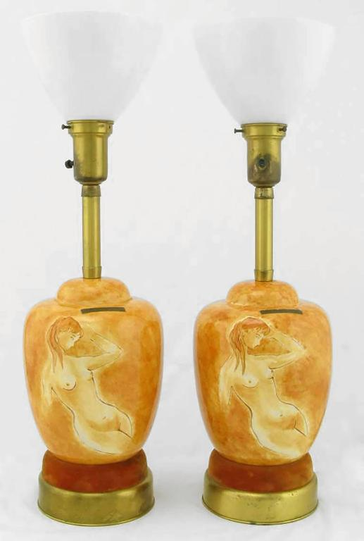 Pair of Sèvres Porcelain hand-painted table lamps with two part brass and umber velvet base. The hand-painted and glazed bodies of the table lamps are a female nude on a heathered cinnamon background. Comes with original milk glass diffusers. Sold