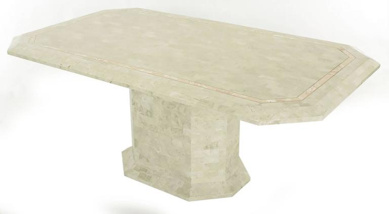 Tessellated fossil stone over wood Art Deco Revival pedestal table with rouge marble and brass inlaid border. Elongated octagon with form following pedestal base. Designed by Robert Marcius and marketed by Casa Bique. Manufactured in the