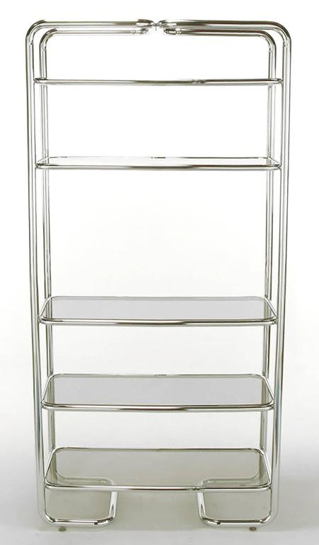 Soft rounded corners and chromed tubular steel étagère in the manner of John Mascheroni. Five shelves with inset smoked glass. Unusual return sled base.