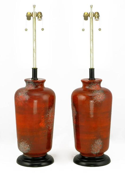 Unique table lamps look as though they were formed from molten lava. Deep textured red glaze over Vermillion ceramic vase form bodies. The bases and stems are black lacquered wood and metal, respectively. Sold sans shades.