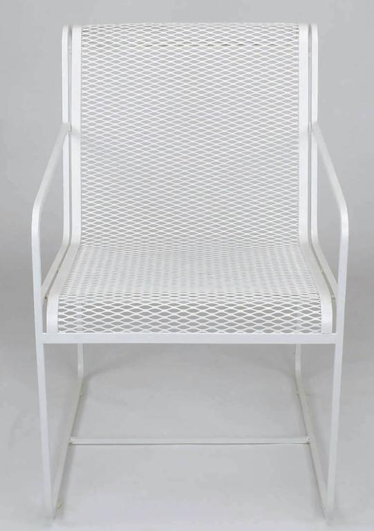 Rare set of four Maurizio Tempestini for Salterini white lacquer over wrought iron framed and iron mesh outdoor dining chairs. Minimalist design with open arms and linear form, iron mesh seat and back flow seamlessly.