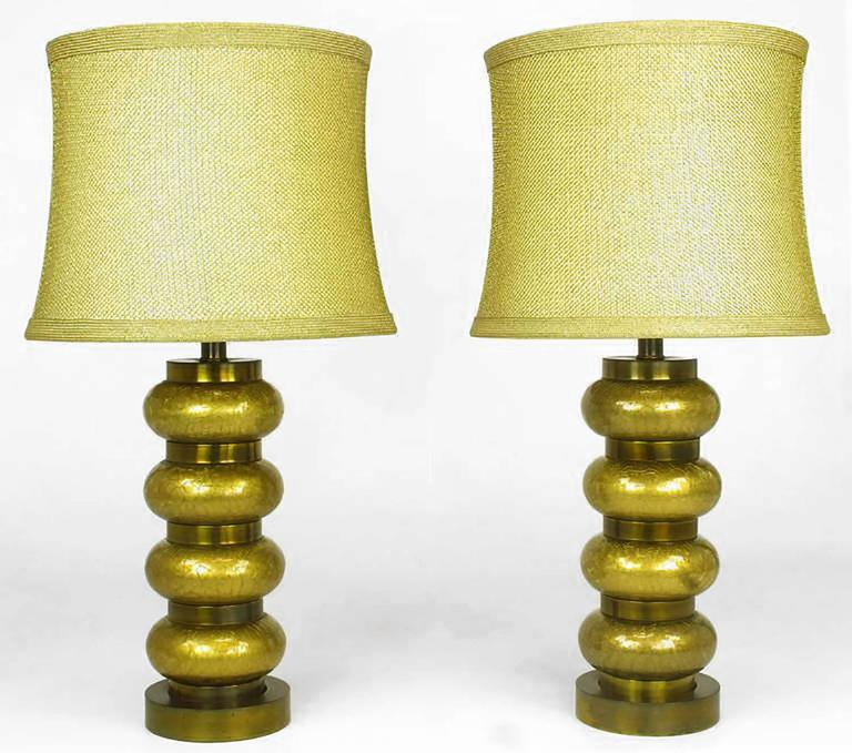 Pair of reverse gilt and brass table lamps by Paul Hanson Co. Inc. circa 1950s. Alternating bands of gilt crackle glass ovals and patinated brass rings combine for sculptural form. Original extra large milk glass diffusers and gold fishnet shades.
