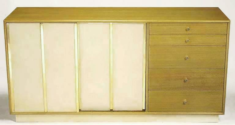 Harvey Probber bleached mahogany long dresser with ivory leather-clad sliding doors and plinth base. Three brass flat bars detail each leather door, giving the appearance of four sections. Behind sliding doors are four additional drawers and three