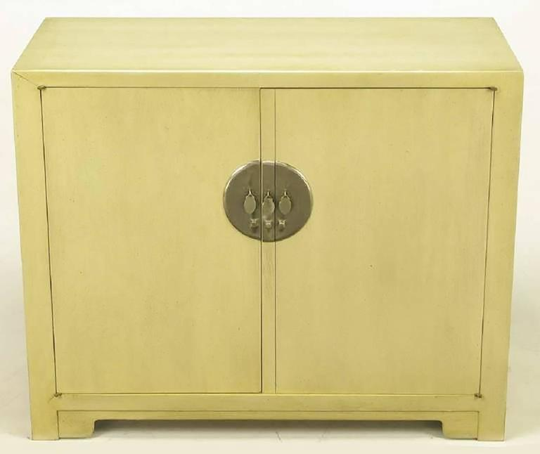 Pair of Baker Asian inspired two-door cabinets, from Winsor White's Far East Collection. One cabinet features three drawers and the other has open shelf storage. Large round nickel escutcheons and drop disc pulls are exceptional. Bases feature