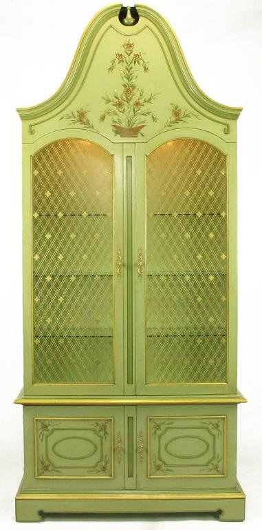 Uncommon John Widdicomb hand-painted French Regency display cabinets in exaggerated fanciful form. Gilt cross hatch wire insert doors with quatrefoil detail. Illuminated interiors, glass shelves and gilt details. Hand-painted floral detailing to