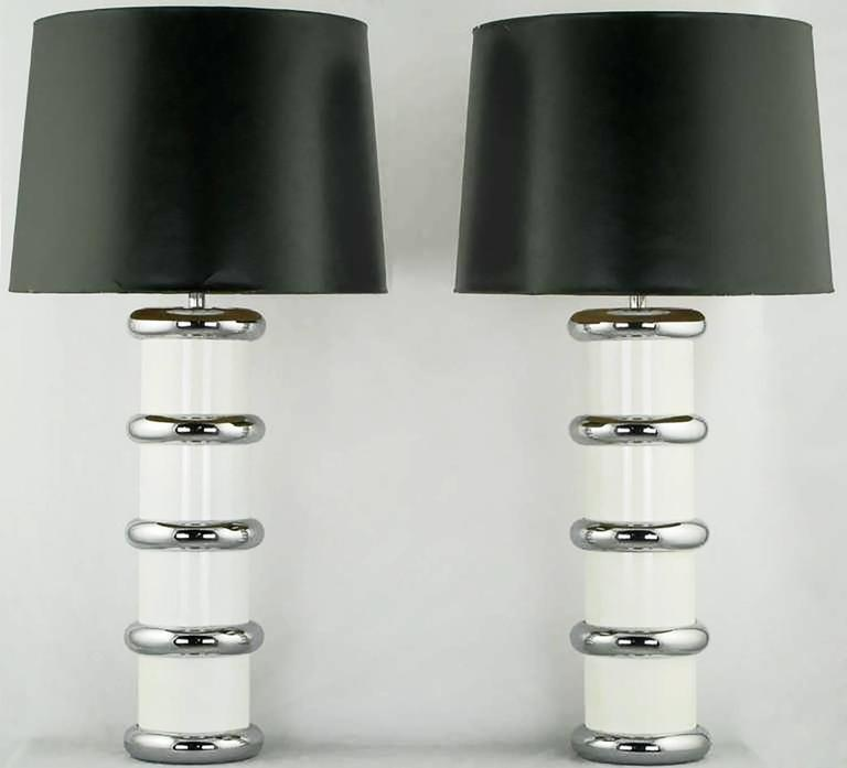 Pair of tubular form table lamps in white enameled steel with chromed steel cuff rings, stem, socket and harp. From the mutual sunset lamp company; a now defunct lamp company that featured designs by Gilbert Rhode, among others. Sold sans shades.