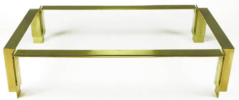 Architecturally inspired Postmodern coffee table constructed of solid brushed brass inward angle legs and floating U-shaped flat bar supports. Well made and heavy, with half-inch thick excised corners glass top. From an estate with many custom items