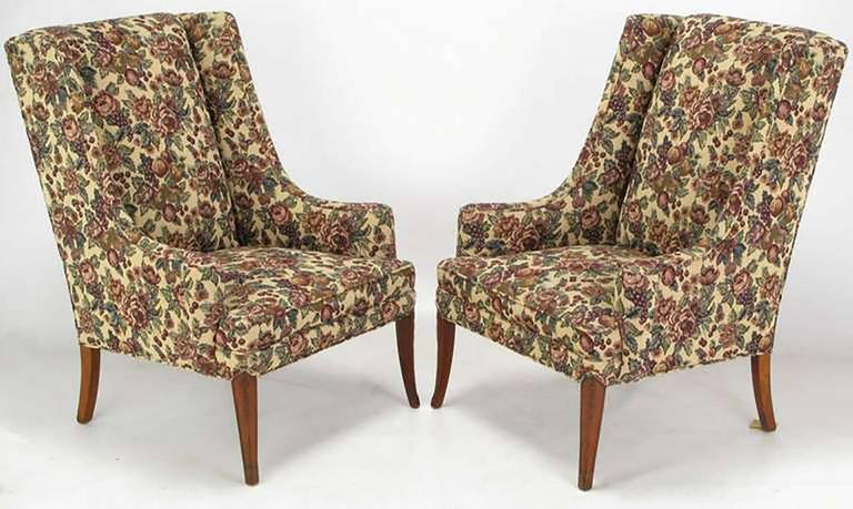 Pair of circa 1940s low arm wing chairs upholstered in a fruit and foliage tapestry. Mahogany saber legs have a lightly carved detail. In a similar style to early Grosfeld House with low turned arms and exaggerated rake to the chair back.