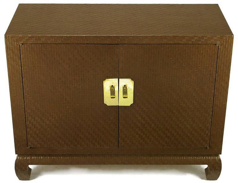 Baker Asian modern cabinet in chocolate lacquered Grassclotha chocolate brown lacquered grasscloth cabinet from Baker's Far East collection. Ming style turned legs and large brass escutcheons backing solid brass drop pulls. The lacquered grass cloth