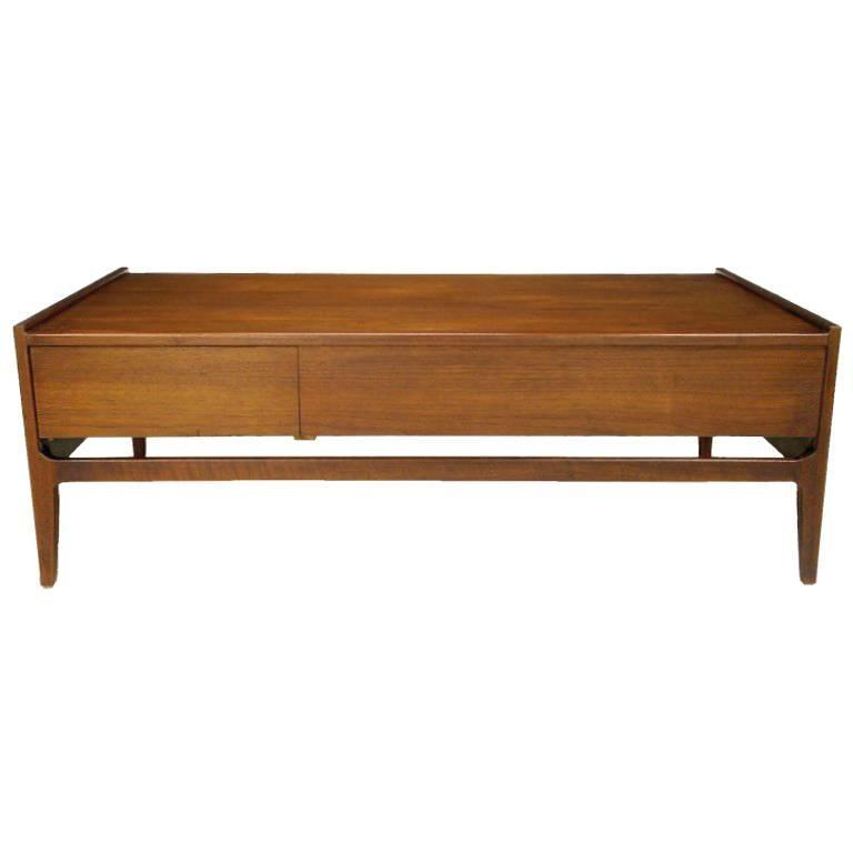 This clean lined coffee table by Richard Thompson reflects California Modern at its best. Constructed of walnut and oak, and finished in walnut veneer, the table features a concealed flush drawer for storage.
