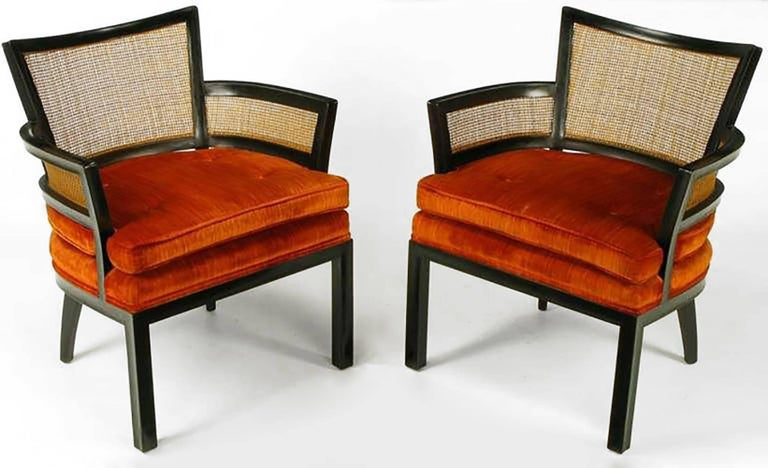 Pair of ebonized mahogany and cane arm chairs by Baker Furniture. Stacked and loose seat cushion is upholstered in a button tufted persimmon velvet. Most likely a Michael Taylor or Winsor White design.