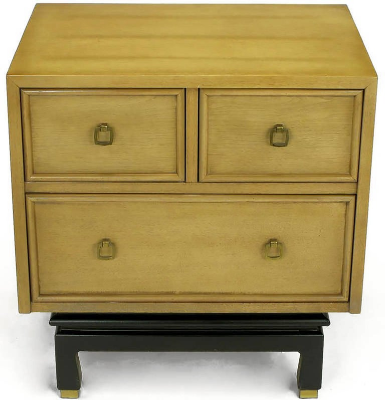 Pair of bleached and glazed mahogany chinoiserie nightstands or end tables with recessed picture frame drawer fronts. Drop ring brass pulls are squared and sans escutcheons. Black lacquered and recessed four leg platform base with brass sabots.