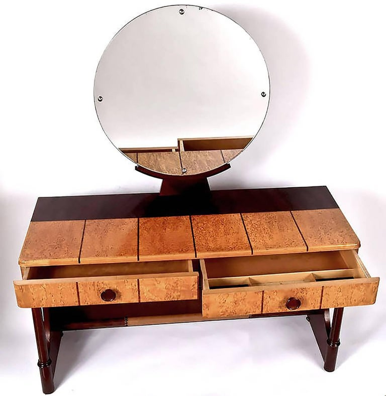 Striking Art Deco vanity constructed of dark mahogany and lighter burl, by the fine Danish furniture maker, Robert Rasmussen. Darker strips inlaid in the burl, with leather wrapped footrest. Round mirror mounted on curule base.  Measure: Vanity