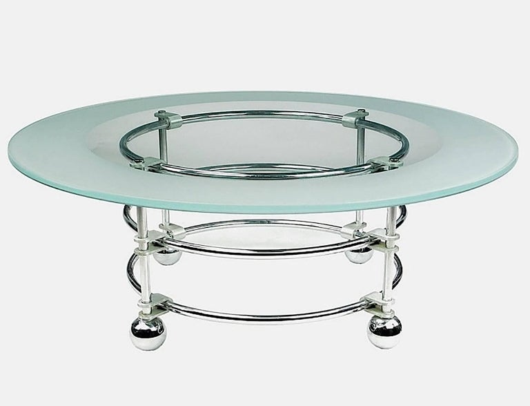 An uncommon Jay Spectre round coffee table for Century Furniture. The chromed steel base is held together with cast aluminum U-brackets. Spherical feet, also in chrome. One-half inch thick glass top is clear with a wide acid etched border.