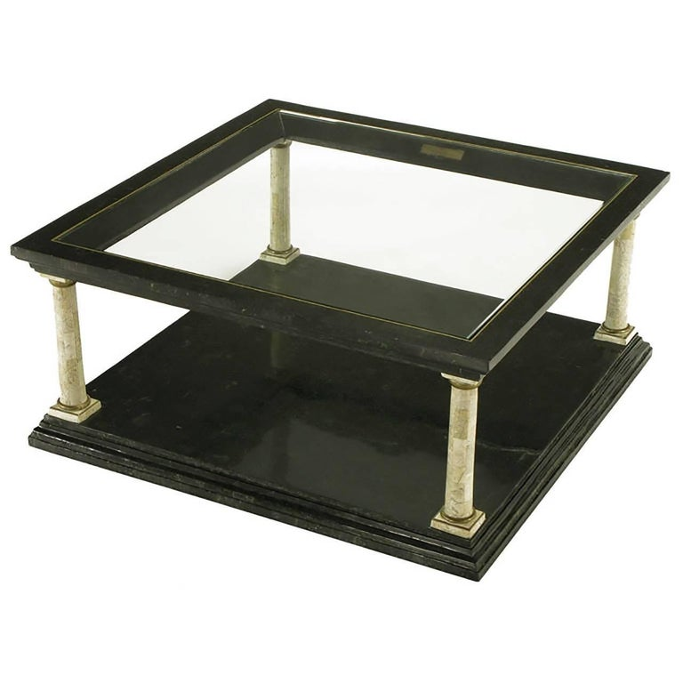 Features four Doric columns, with shafts of creamy tessellated fossil stone, atop a black tessellated marble base. The columns, with brass capitals and base rings, support the upper part of the table, which is also black stone. It has brass trim