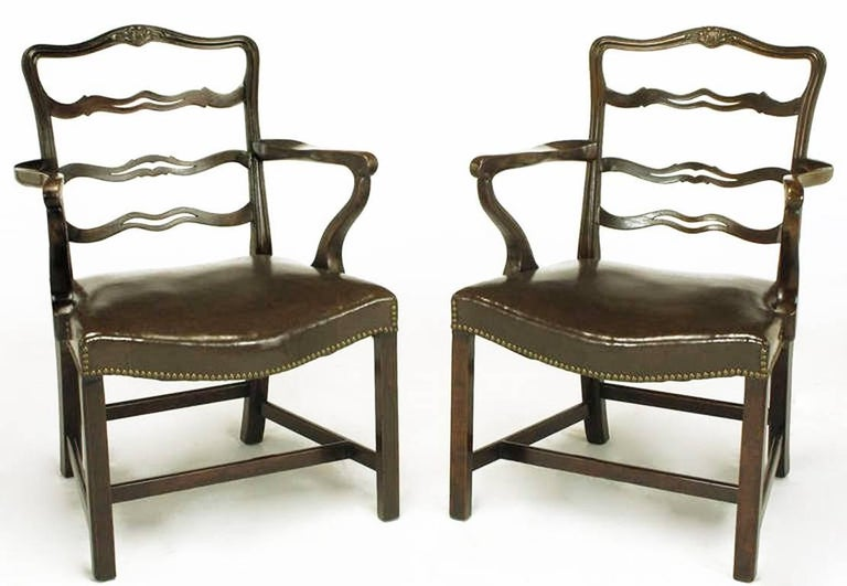 Finely reproduced pair of walnut George III armchairs. Ribbon backs with sinuous arms and a brown leather-like bow front seat with brass nailhead tacks. Four part stretcher with beaded legs. American made.