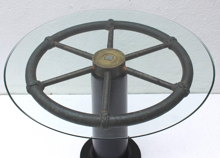 Wonderful and unique nautical table created with authentic ship's wheel mounted on ebonized wood pedestal base with a glass top.
