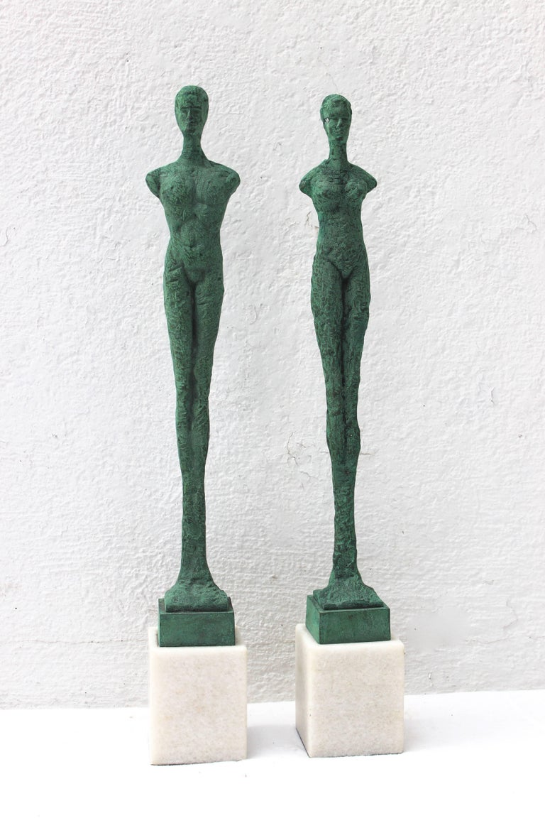 Wonderful pair of patinated bronze Giacometti style figures mounted on marble block plinths.  Male figure measures 20.75
