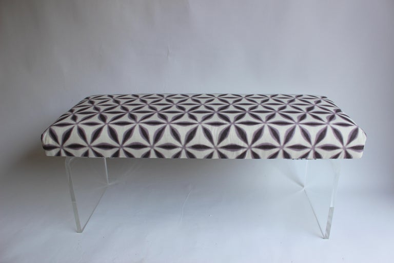 Newly upholstered bench with lucite waterfall legs......fabric is a printed linen from Michael Smith.