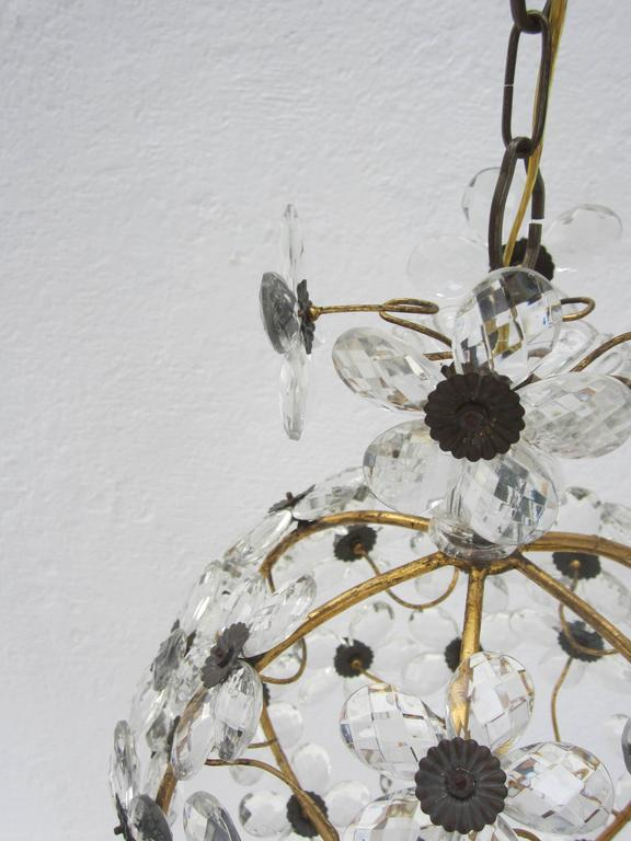 Unique globe pendant made up of crystal flowers with a gilt wrought iron frame.