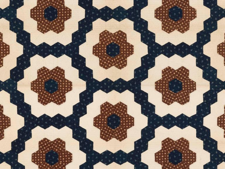 """Mosaic Hexagons"" with ""sawtooth"" border. Pieced quilt, mid-19th century, American. Fancy period calicoes left over from fancy clothing and decorating fabrics are pieced in hexagon shapes to form this large, elegant, bedcover. The elaborately"
