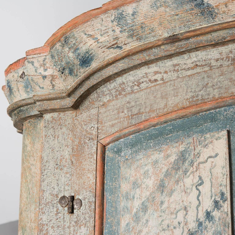 This cupboard, from an area northwest of Stockholm, was made by a master craftsman and artist. The combination of faux grain painting in blue and coral on the doors is fantastic and all original. This special piece has all the best elements of the