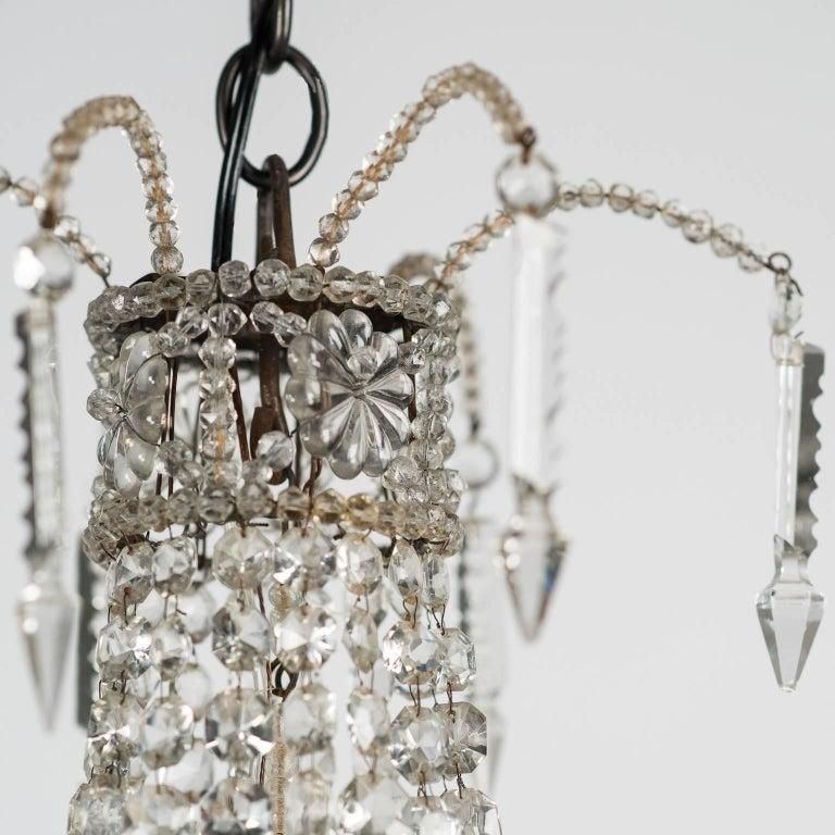 This charming piece has an unusual design with a double band of crystal flowers and swags surrounding the three inner lights. It has been cleaned and rewired for US circuits and is the perfect size for a powder room or bedroom.