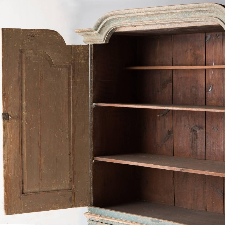 This fantastic cupboard in a perfect shade of all original Swedish blue paint is a rare piece that is hard to find in such great condition. It has a simple curved cornice with the same carving echoed on the doors.