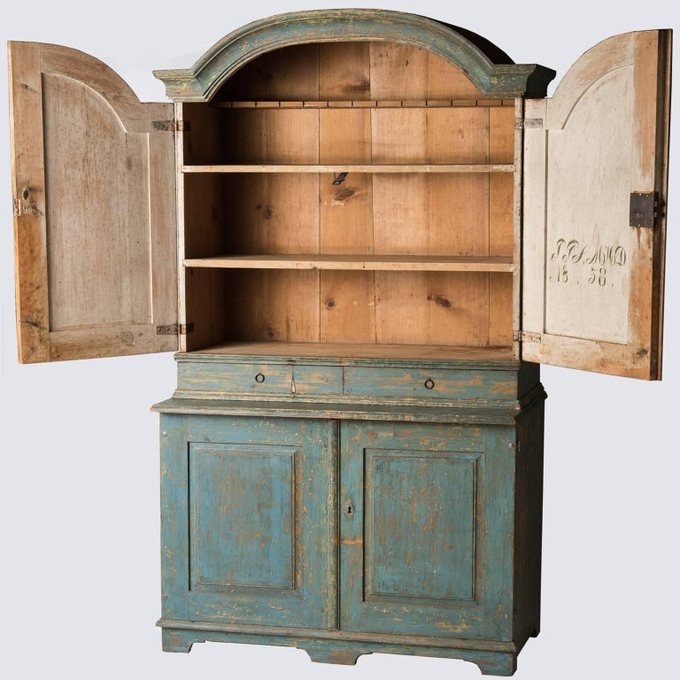 This important cupboard in the Rococo style retains the original blue paint throughout. It has three interior shelves, perfect for storing collections of bowls or china. There are two convenient drawers that could be perfect for silverware and two