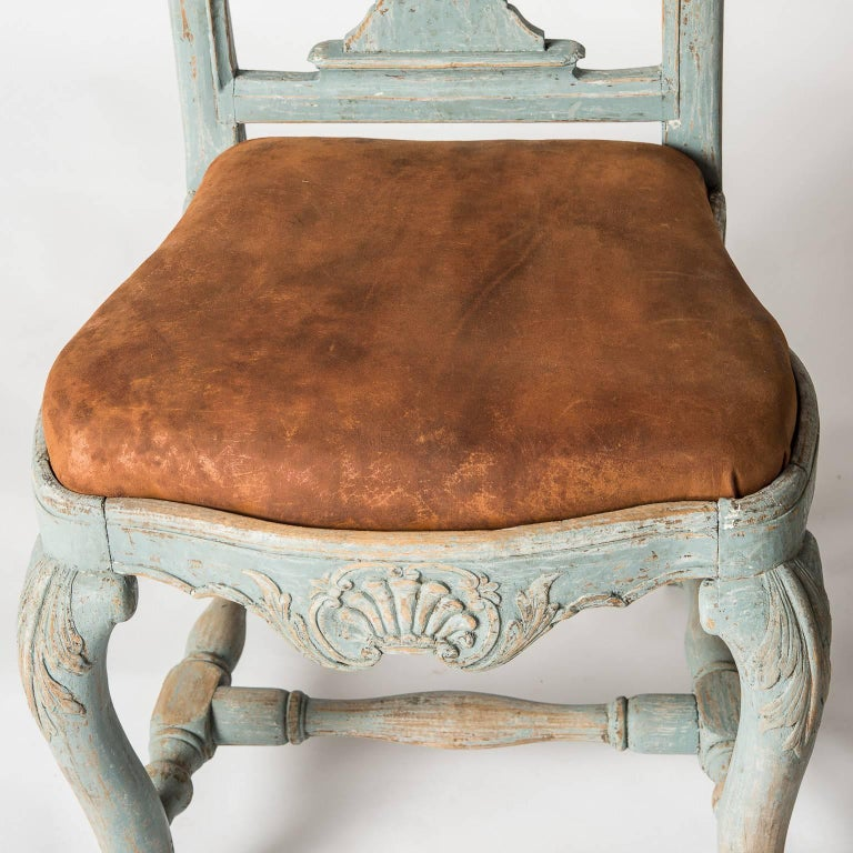 These rare chairs have great form with a fan shaped carving on the crest and old leather seats. The apron echoes the same fan shape as the crest and the legs have intricate carvings at the top and bottom, which is unusual. The old blue paint is a